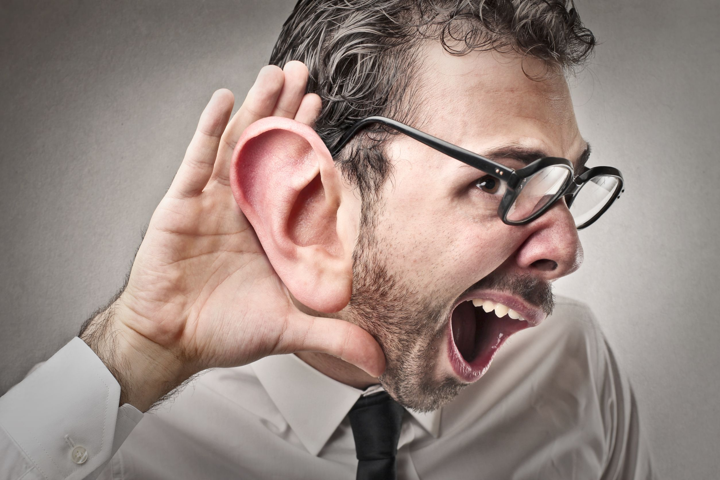19940468 – man trying to hear with a huge ear