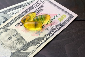 Yellow capsules omega 3, fatty acid, fish oil on dollar banknote at wooden table