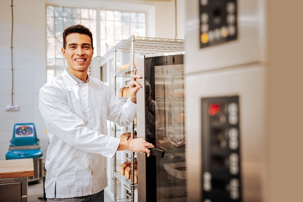 Baker smiling while opening the door on oven and checking bread