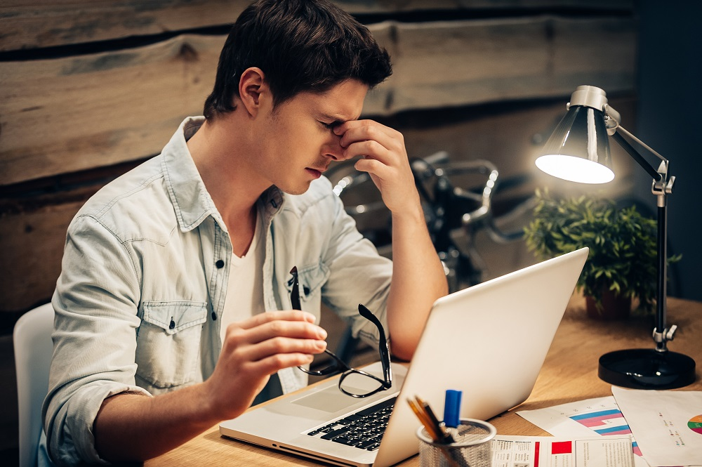 Feeling exhausted. Frustrated young man keeping eyes closed and looking tired while working late at his working place