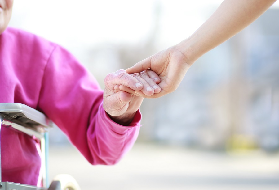 15278660 – senior lady in wheelchair holding hands with caretaker
