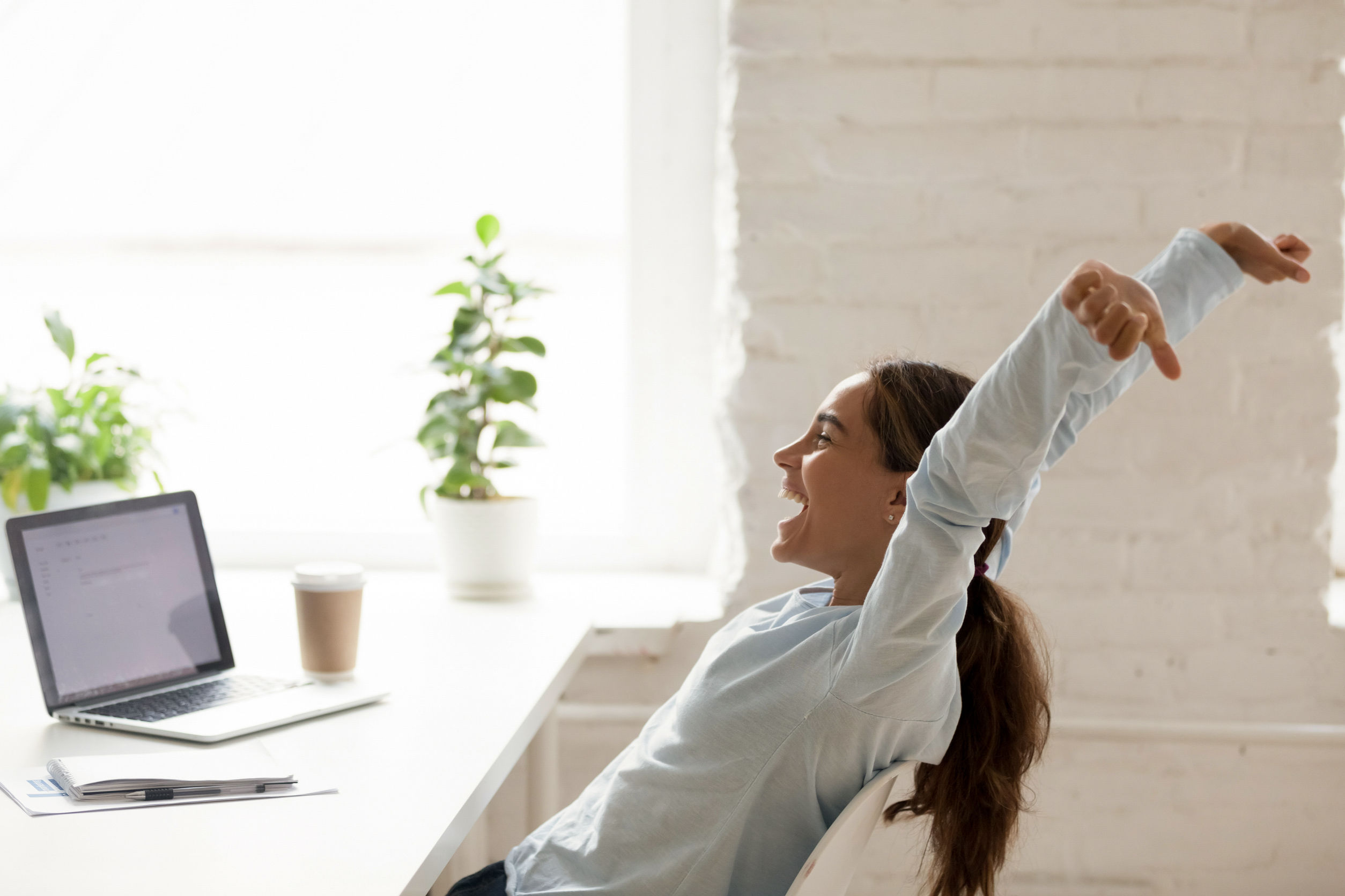 Cheerful woman stretching raising hands up sitting at workplace