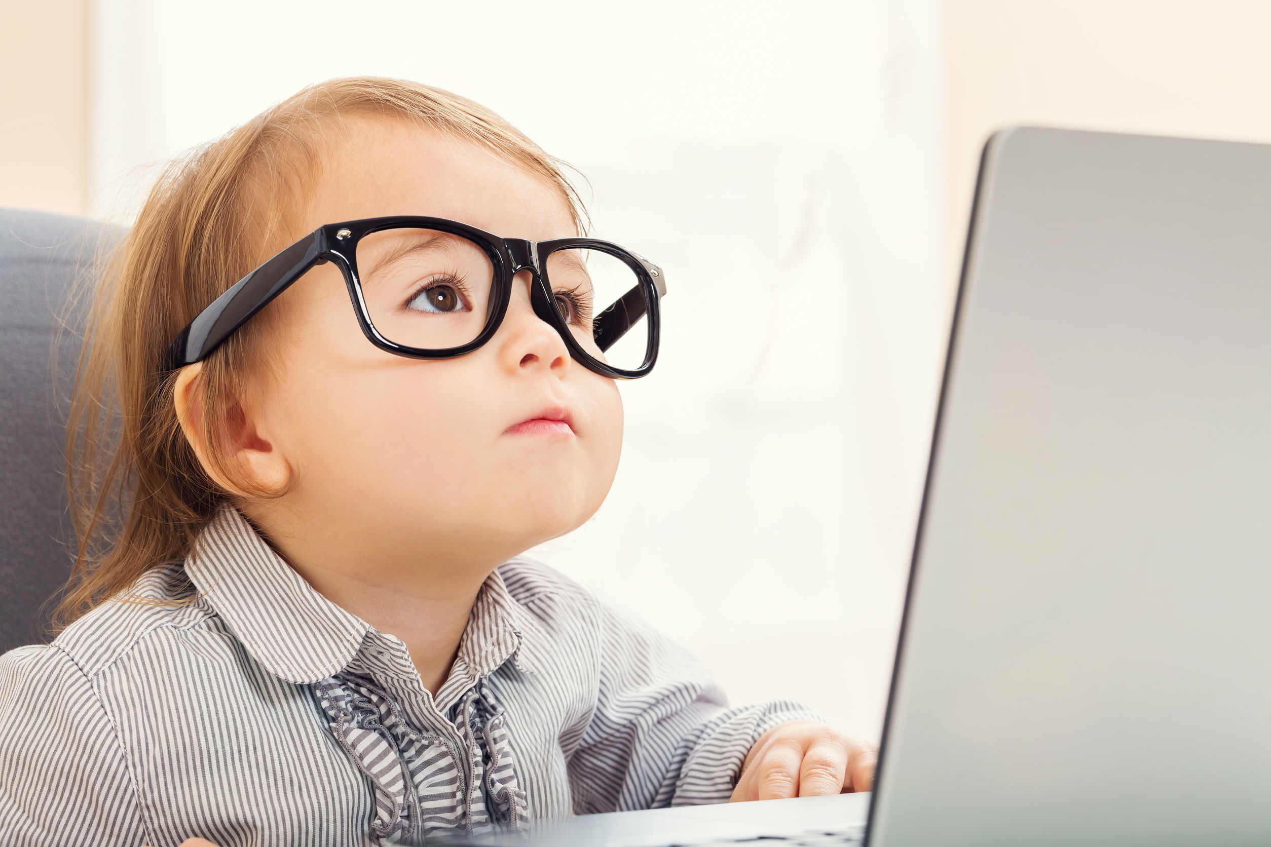 52412801 – smart little toddler girl wearing big glasses while using her laptop