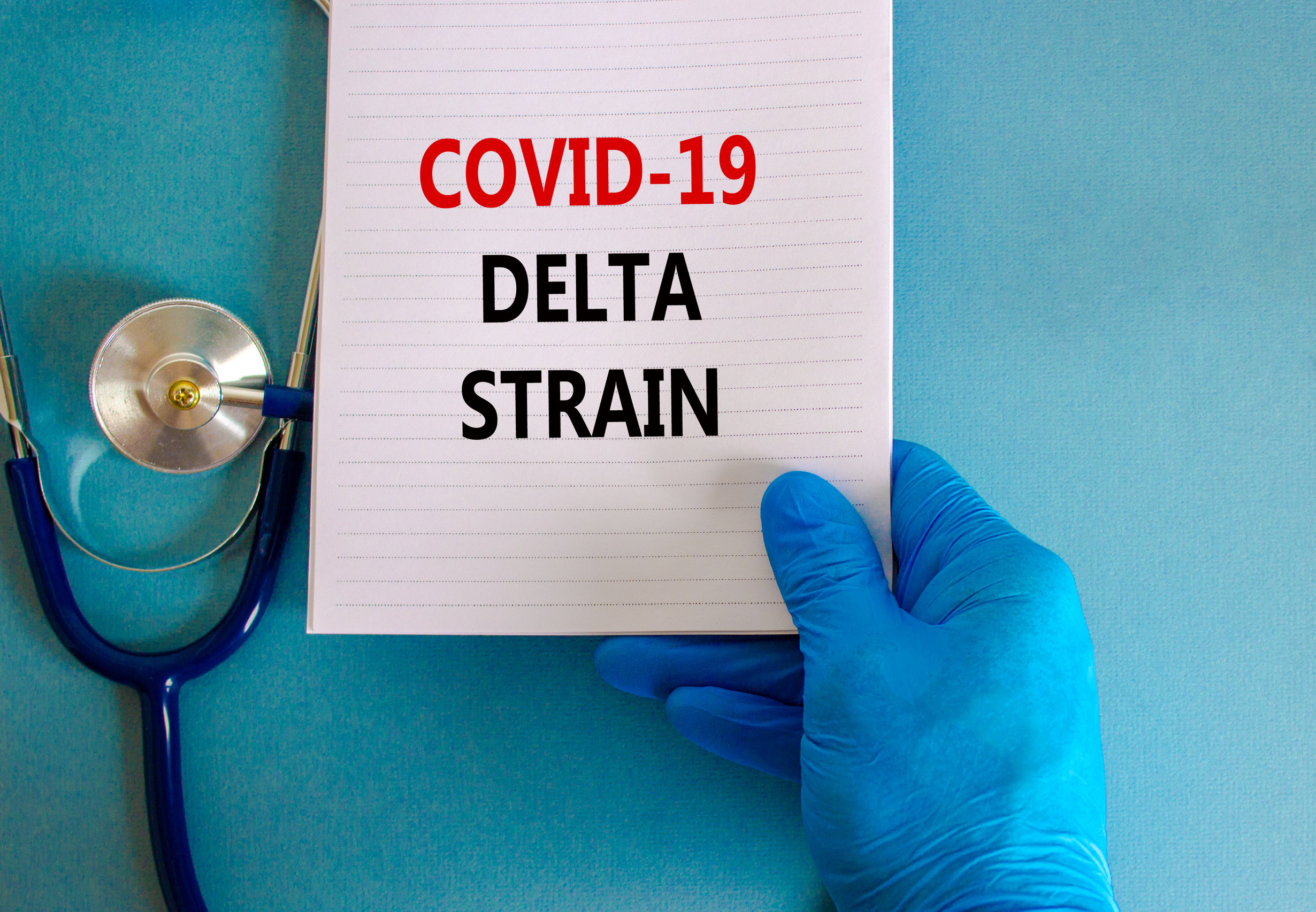 Covid-19 delta variant strain symbol. Doctor hand in blue glove with white card. Concept words 'Covid-19 delta strain'. Stethoscope. Medical and COVID-19 delta variant strain concept. Copy space.